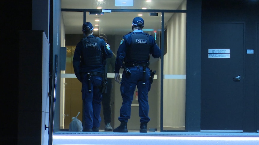 police officers speak to man behind glass automatic doors