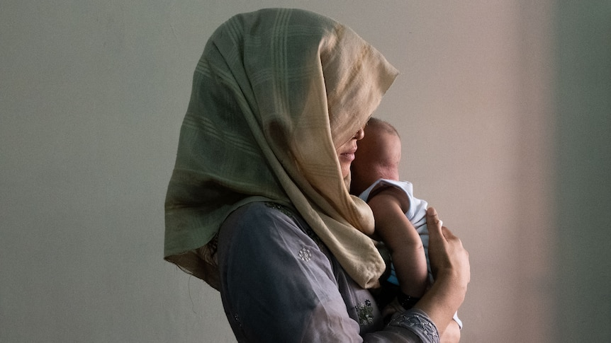 A woman in a headscarf holds a small child close to her chest.
