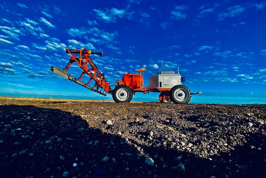 a red tractor liike machine with a spray boom at the back viewed from spoil level and looking at blue sky.