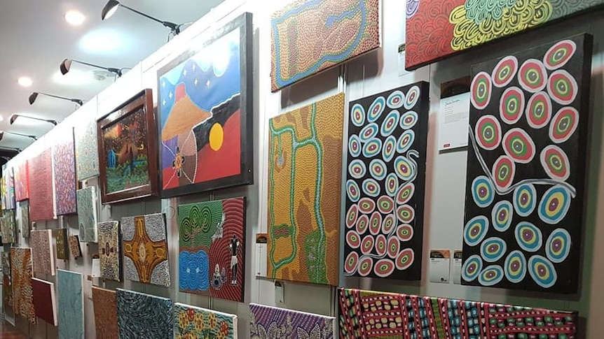 Various colourful Indigenous paintings on a wall.