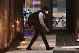 A live export ship crew member with a backpack and face mask on walks away from a Transperth bus at dusk towards a hotel.