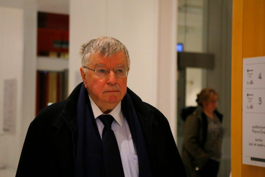 Didier Lombard walks down a corridor wearing a dark suit and glasses.