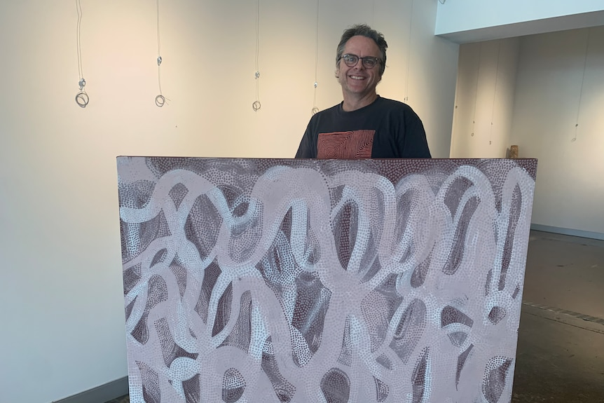 A man holding up a painting in front of his body.