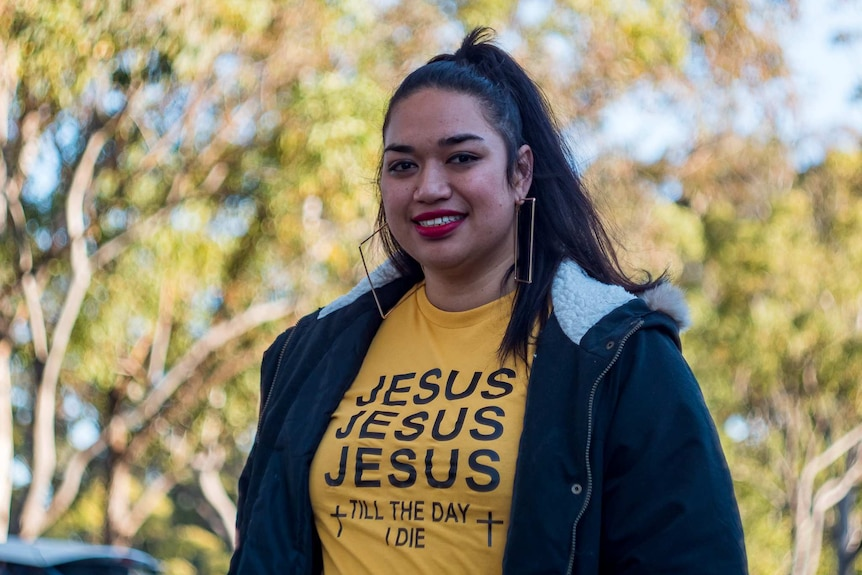 Ana Makahununiu, a Tongan woman, smiling. She is wearing a t-shirt that says 'Jesus Jesus Jesus till the day I die.'