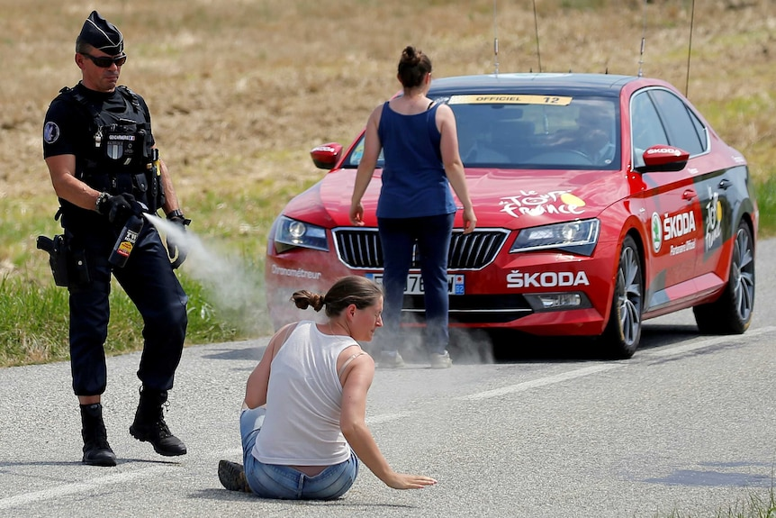 A police officer sprays a protester as another protester stands in front of a red car.