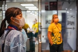 A masked woman in a Tokyo 2020 shirt looks off as an Australian female athlete lingers in the background