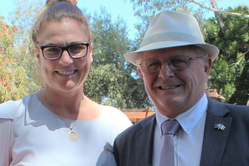 A middle-aged woman in glasses smiles while standing next to an older man wearing a hat and suit.