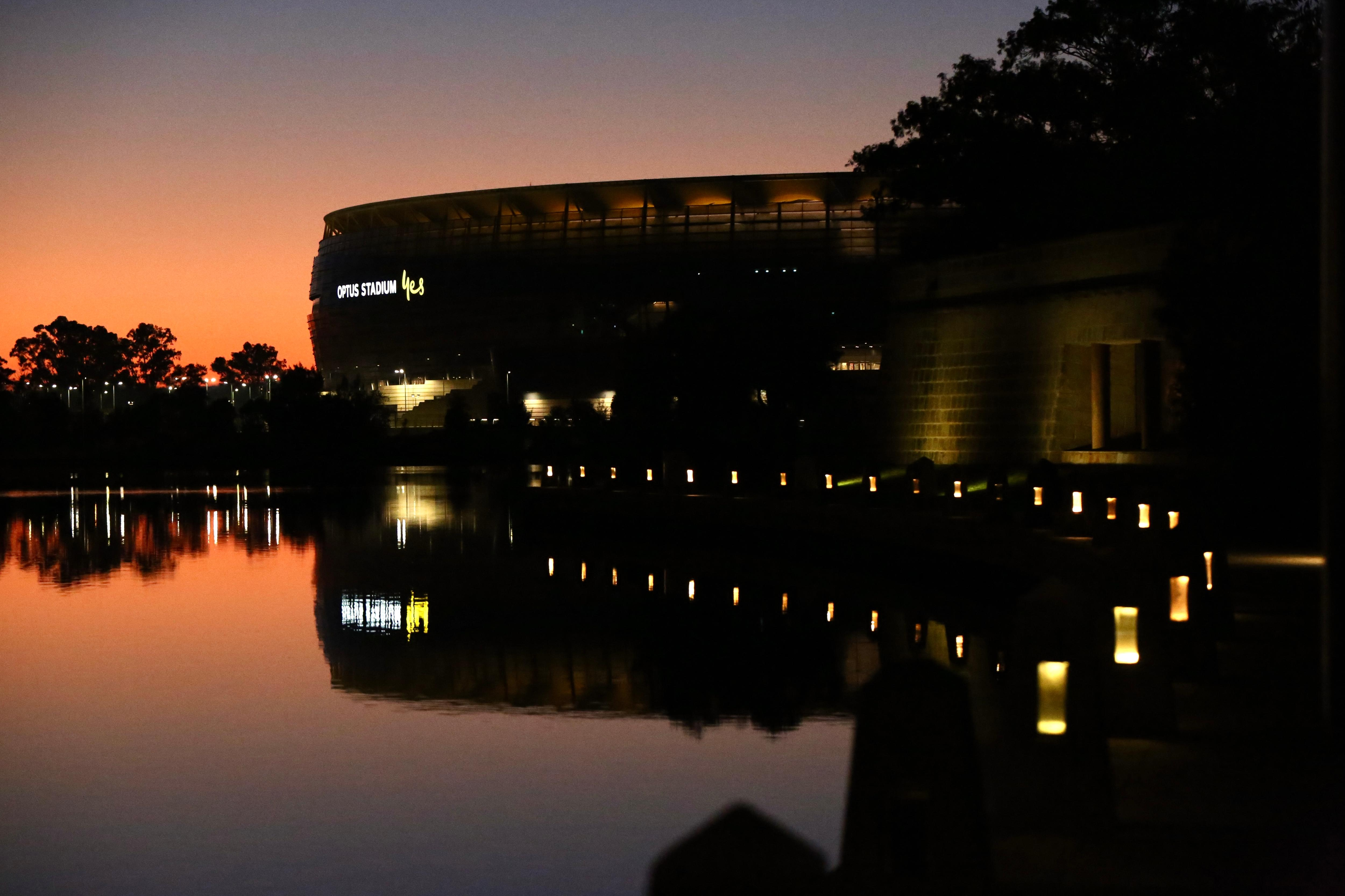 Dawn begins to appear with an orange hue over the Perth Stadium reflected onto the Swan River.