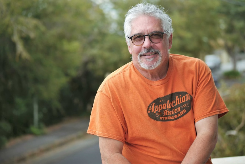 A bespectacled man with grey hair and a goatee wearing an orange shirt.