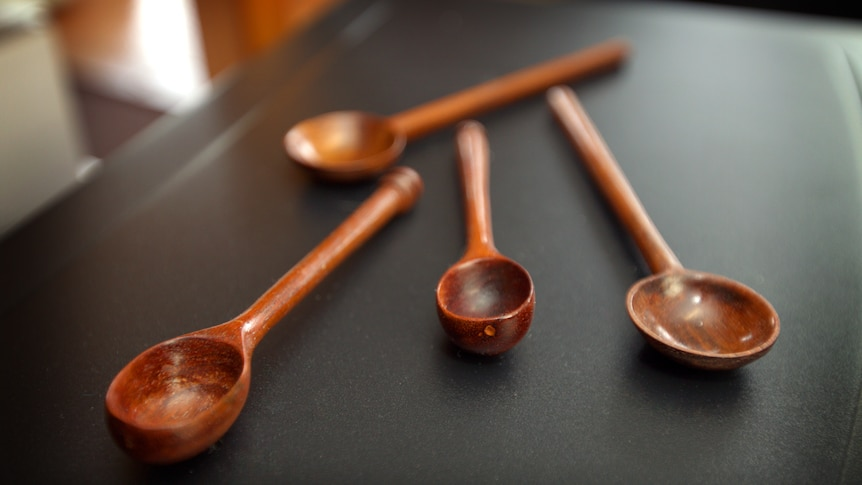 Four spoons made from dark timber sitting on a charcoal coloured surface.