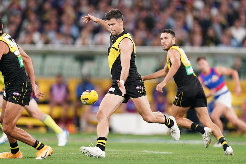 An AFL footballer drops the ball to kick it forwards as he runs down the ground with teammates surrounding him.