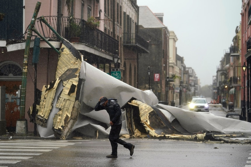 A man covers his head from the rain as he passes a section of roof that has been torn off a building by hurricane winds.