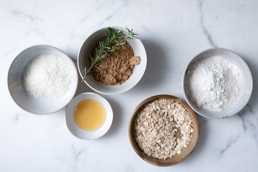 Anzac biscuit ingredients laid out in bowls with desiccated coconut, brown sugar, rosemary, honey and plain flour, ready to bake