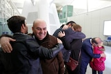 A family embrace before boarding a flight from Iraq to the US