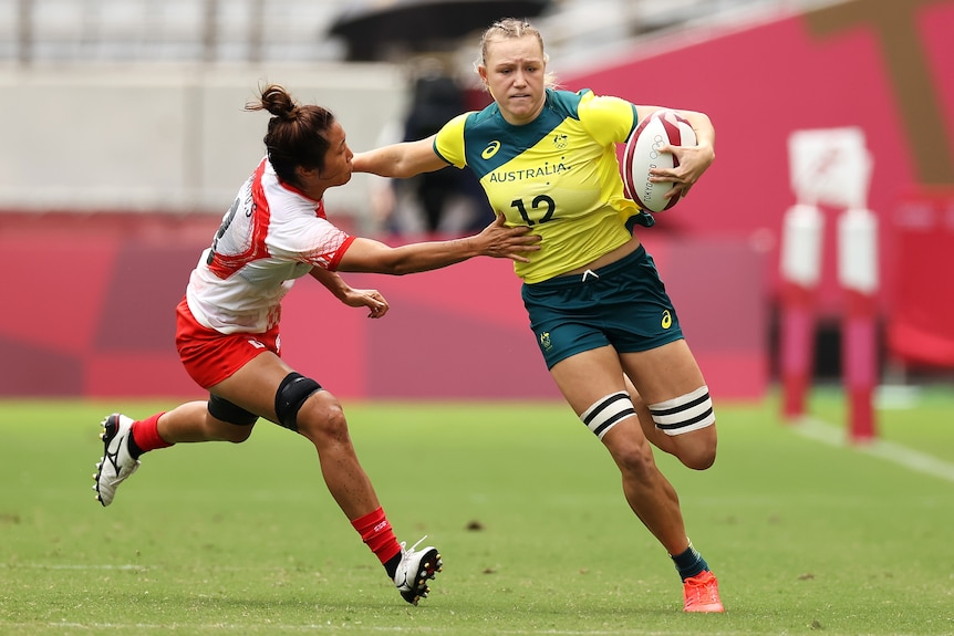 Australia's Maddison Levi storms past a Japanese opponent in rugby sevens at the Tokyo Olympics