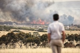 Fire in the background with a man standing looking on