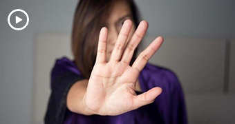 Woman with hand outstretched, obscuring her face.