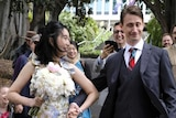 A Chinese woman and an Australian man walking in the Botanical Gardens and smiling.