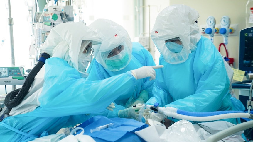 Three doctors and nurses wear protective equipment as they treat a patient in a hospital room.