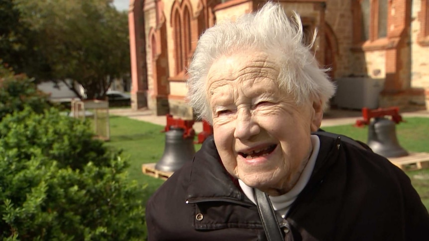 An elderly woman with white hair, with church bells on the grass and a church in the background behind her.
