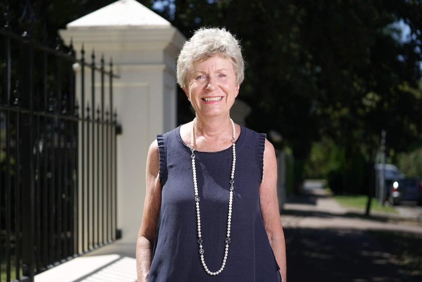 A woman in a navy dress stands on a path smiling