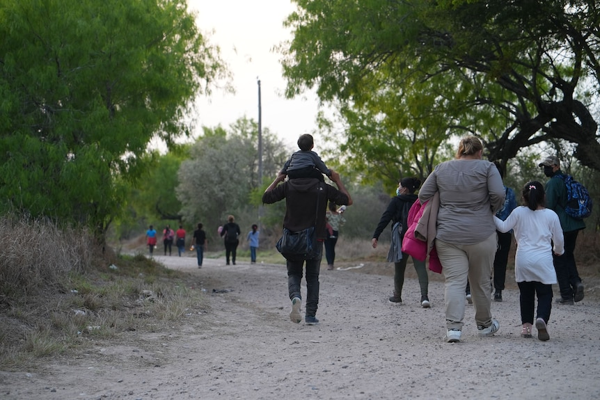 A group of people walk along a sandy path.
