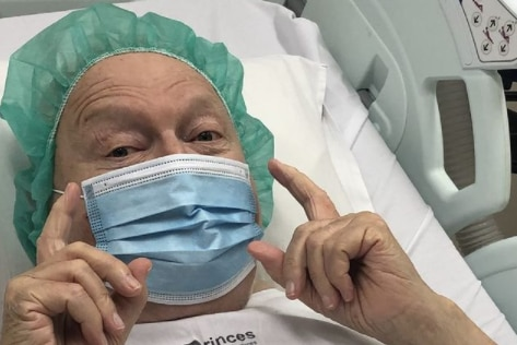 Bert Newton poses for a photograph, wearing a hairnet and blue surgical mask.