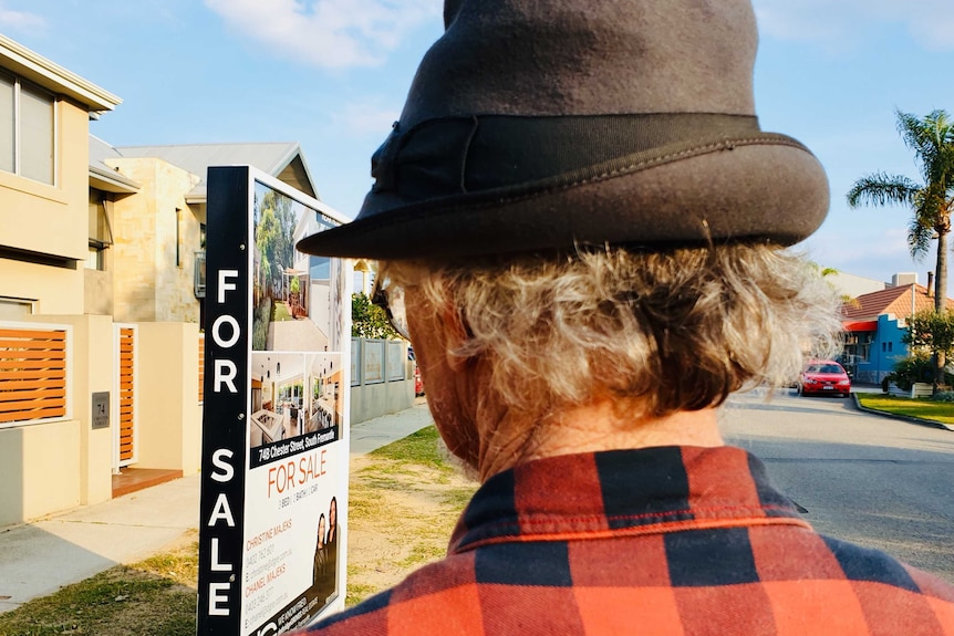 back of man's head, wearing grey hat, looking at for sale sign in street