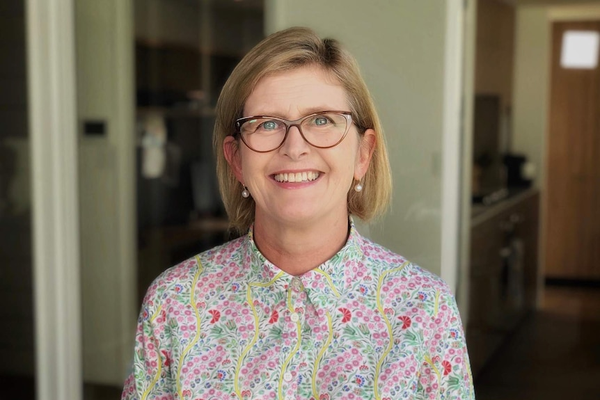 A woman wearing glasses and a floral shirt smiles at the camera.