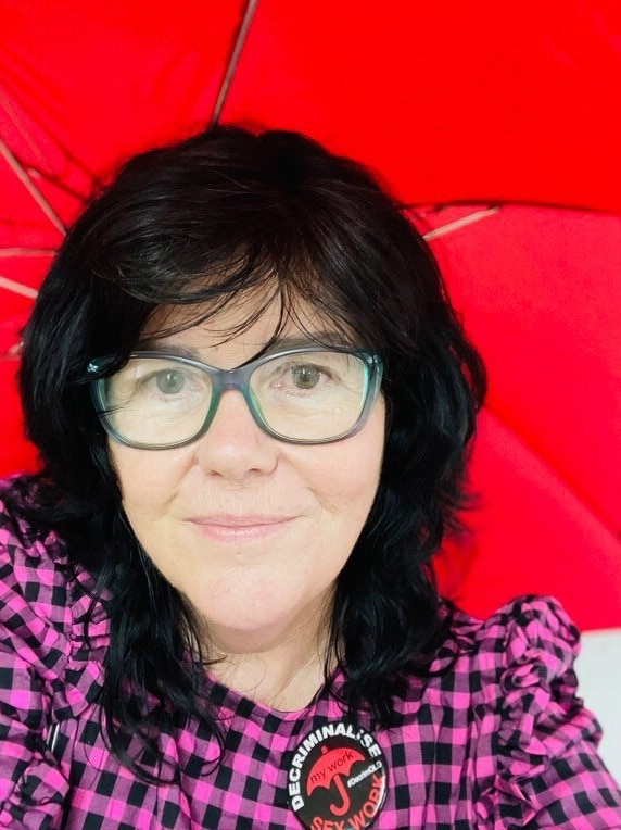 A woman smiles underneath a red umbrella.
