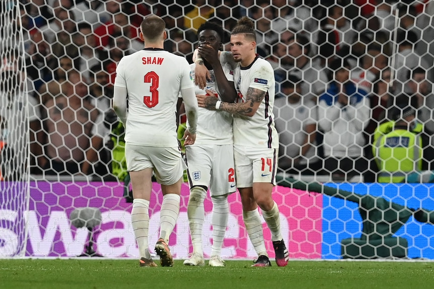 Bukayo Saka holds his hand to his mouth and is hugged by Kalvin Phillips