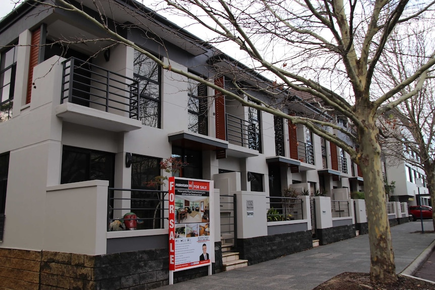A line of townhouses, one with a for sale sign in front. The trees are bare and the sky is grey.