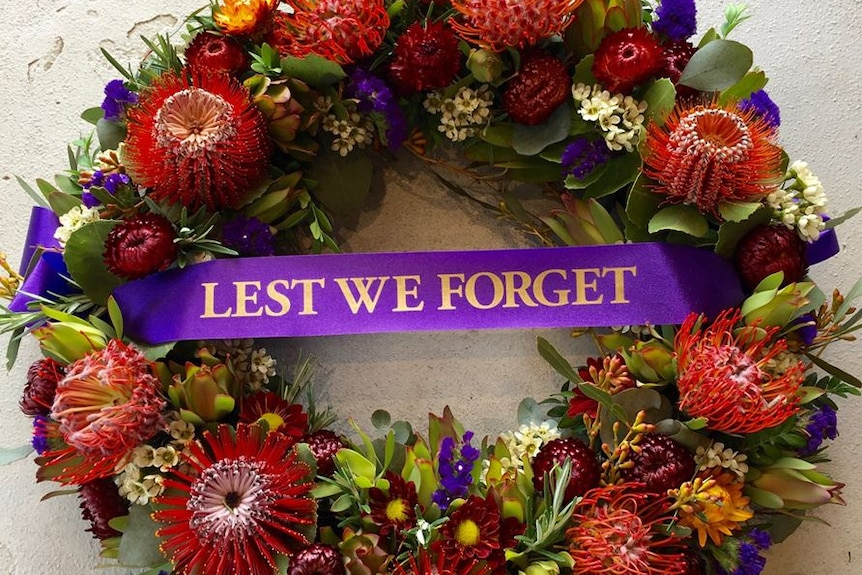 "Wreath with 'Lest we forget"" banner."