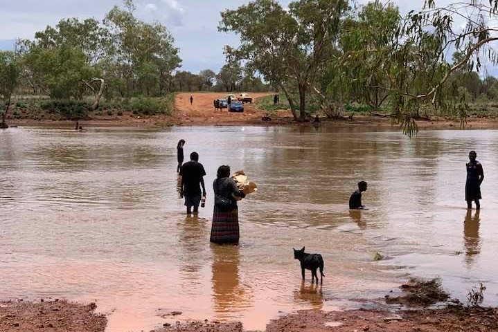 People try to negotiate a glooded river