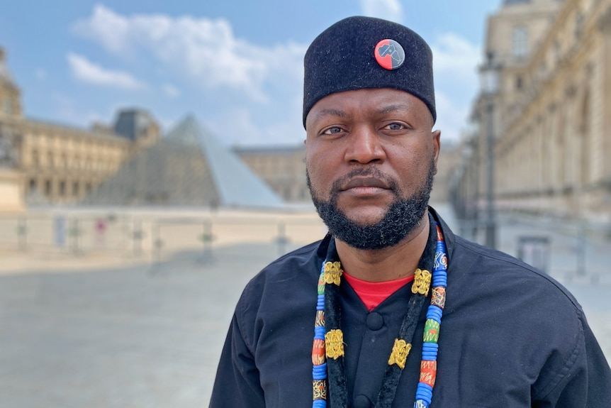 A man with the Louvre pyramid in the background.