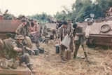Dozens of soldiers mingle and recoup surrounded by tanks, Vietnam 1971.