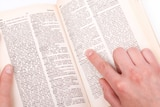 A woman's hand points to a word in a dictionary.