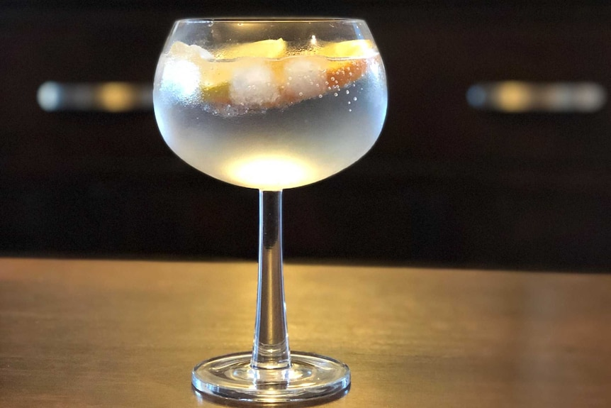 Gin in a glass sitting on a bar.