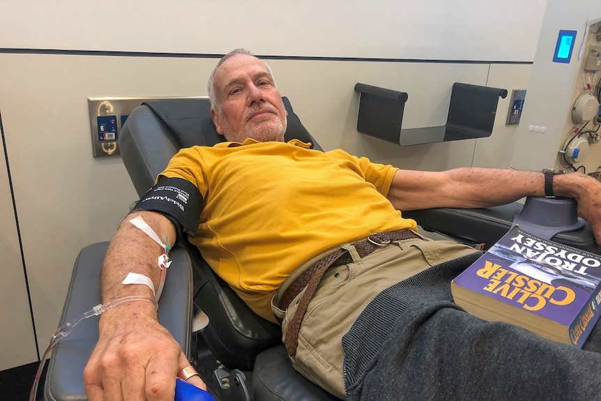 An older man in a yellow t-shirt lying back in a chair giving blood.