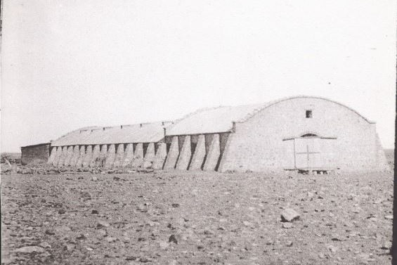 A long stone shed with a curved roof stands in an open plain of gibber rock with a double wooden door on the front