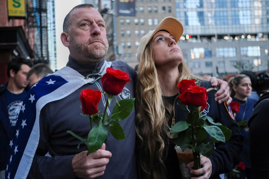 A man and woman looking upward while holding a red rose.