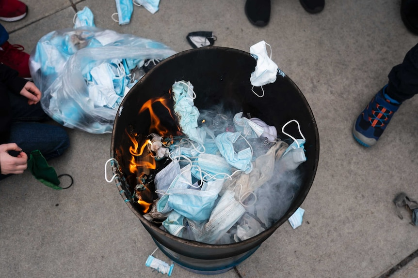 An overhead shot shows a barrel full of disposable blue face masks being burned.