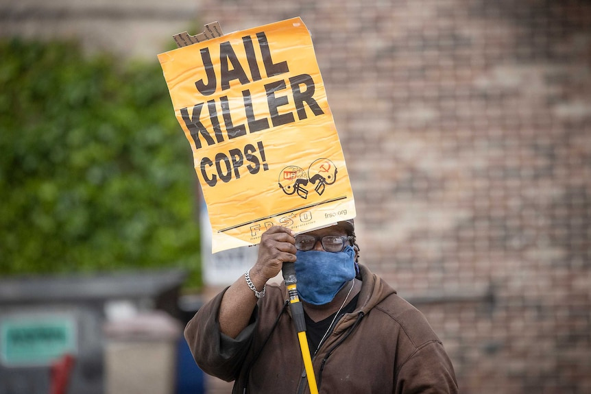 A man wearing a face mask holds a yellow sign saying 'jail killer cops'.