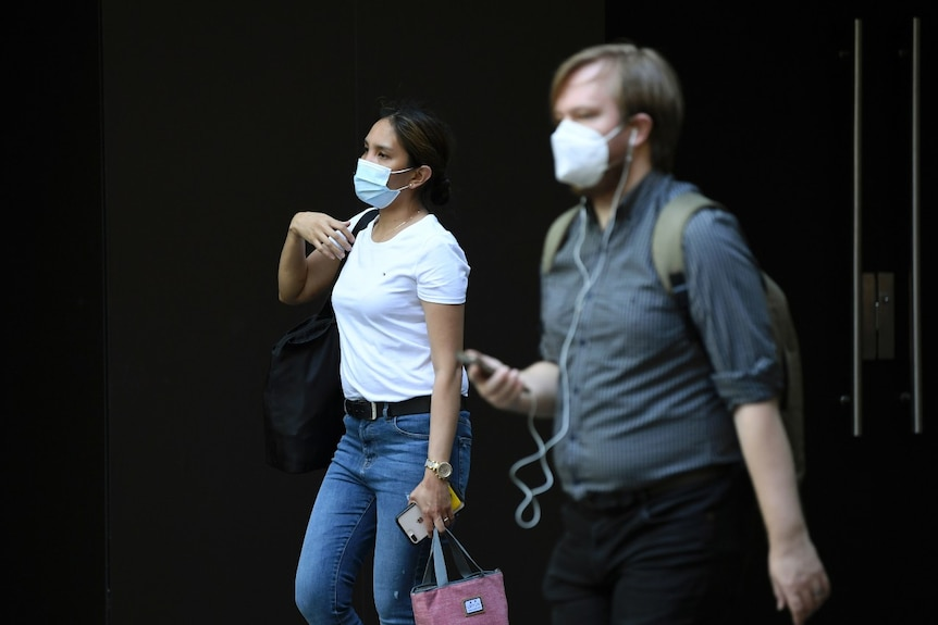 A man and a woman wear masks while walking in the city.