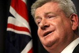 Headshot of Mitch Fifield speaking at a podium with an out of focus Australian flag behind.