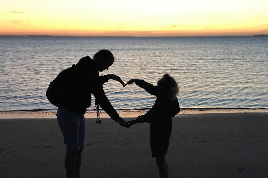 A woman and child on a beach at sunset making a heart with their arms.