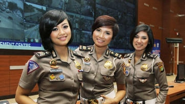 Three female police officers stand in front of a large screen wearing uniforms