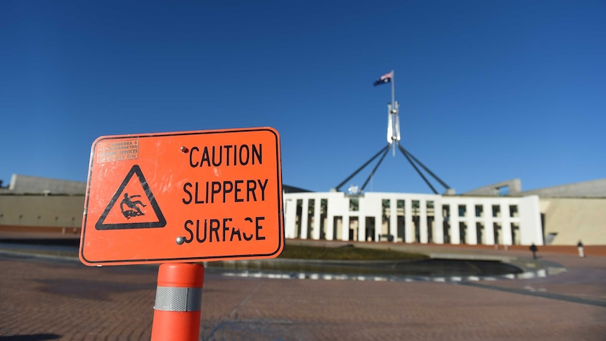 """A """"caution slippery surface"""" warning sign is seen outside Parliament House,"""