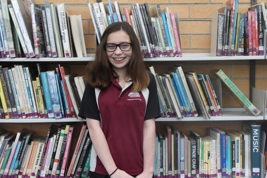 Oriana Watts stands in front of a book shelf at Toormina High School.