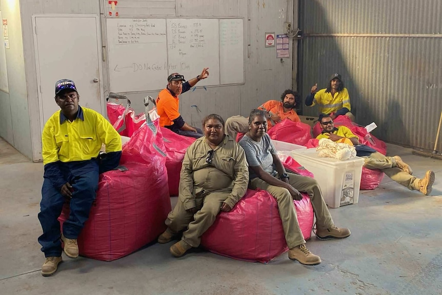A group of East Kimberley residents sit on bags of collected seed inside warehouse